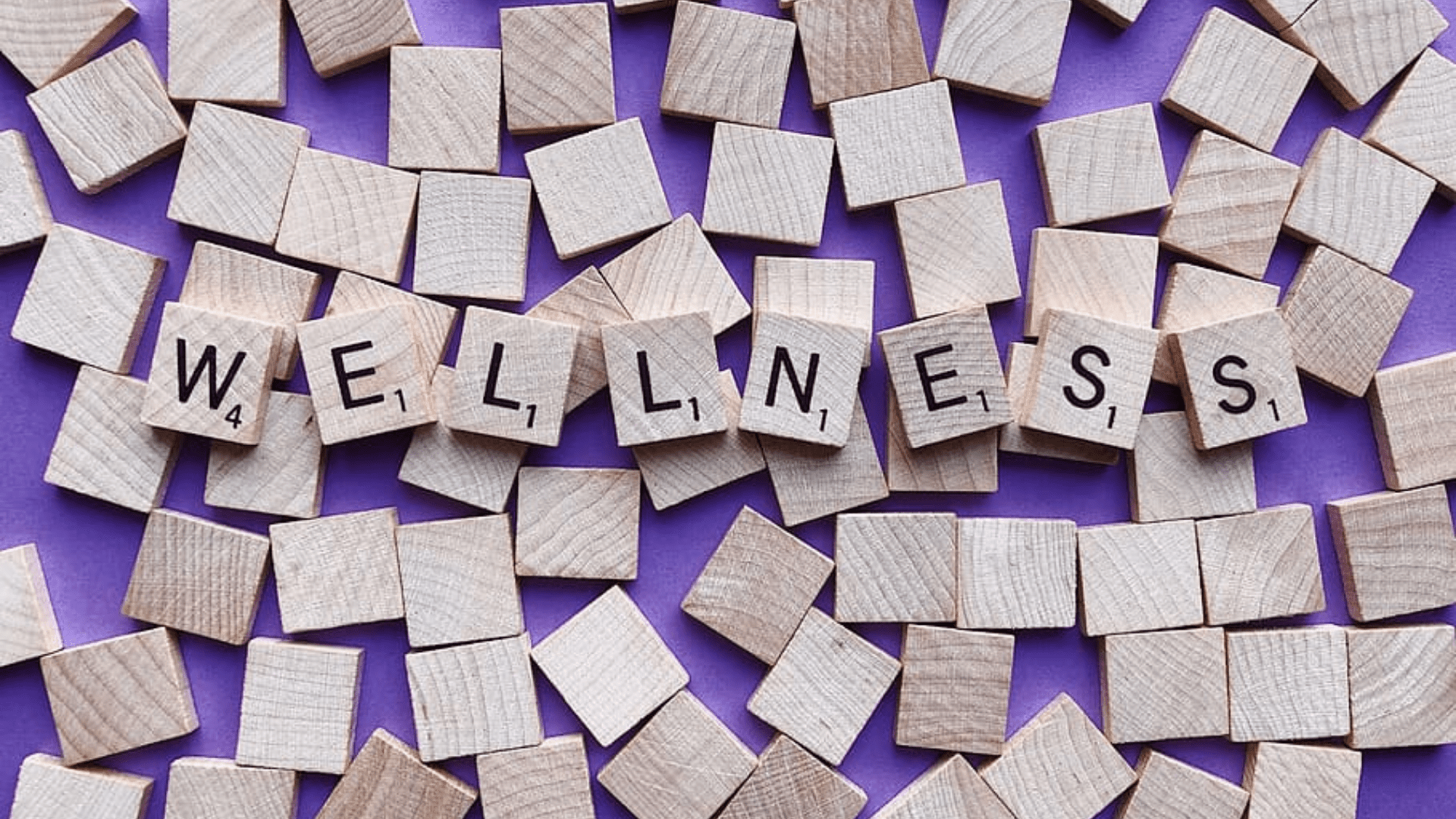"letter tiles spelling ""wellness"""