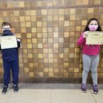 elementary students holding Kindness Certificates