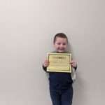 elementary student holding Kindness Certificate