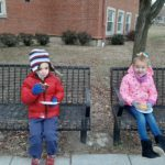 two elementary students seated on a bench enjoying donuts