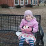 an elementary student seated on a bench enjoying hot cocoa