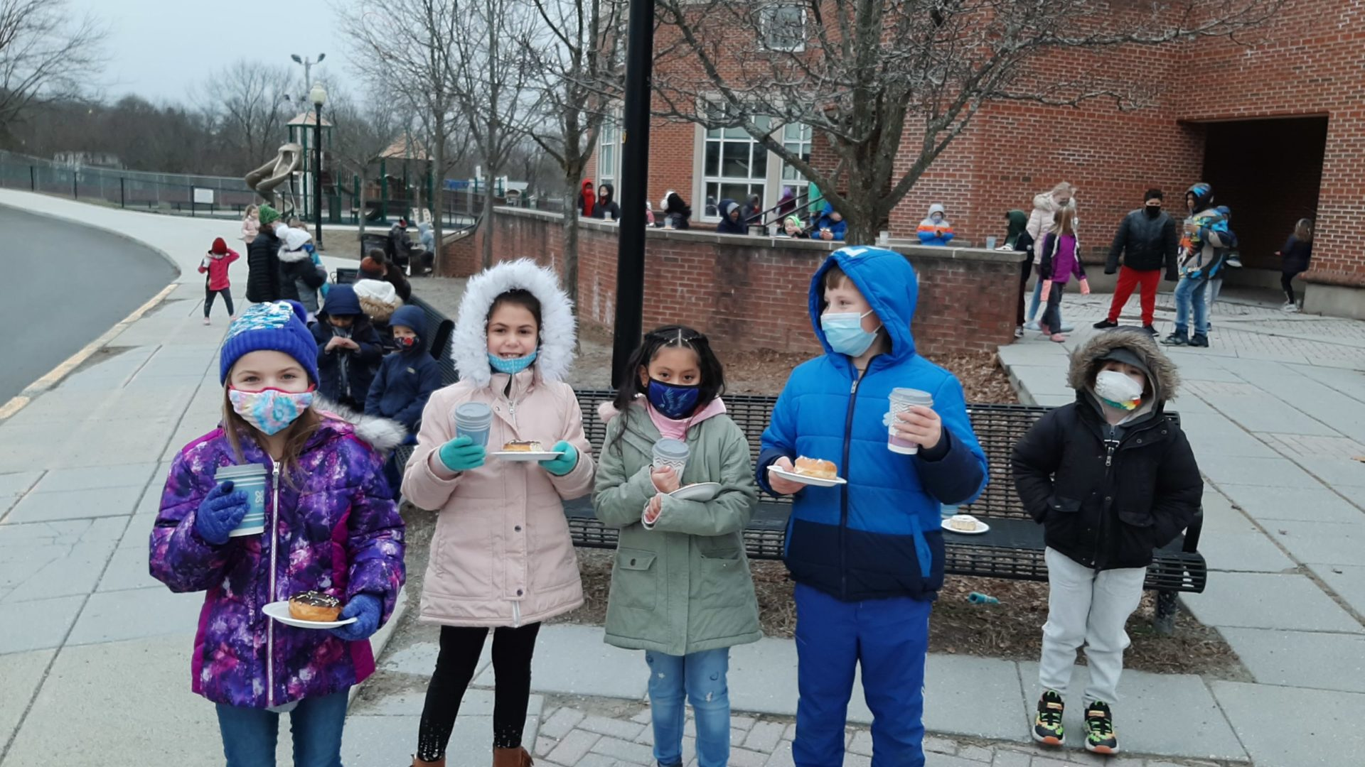 a group of elementary students outdoors enjoying donuts and hot cocoa