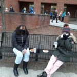 two elementary students seated on a bench enjoying donuts and hot cocoa