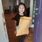 elementary student receives envelope with a certificate and t-shirt