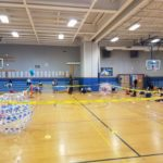 children in gym surrounding a taped off area