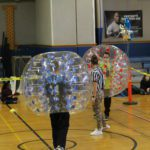 principals do a sumo bubble tournament in the gym