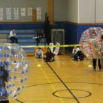 children in gym watching principals do a sumo bubble tournament