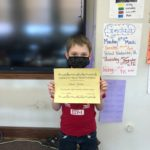 elementary student holding Honesty/Trustworthiness Certificate