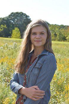 Emma Johnson standing in field of flowers
