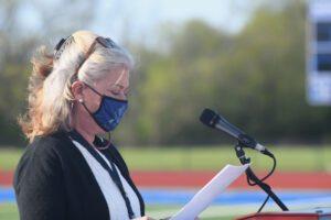 woman speaks at outdoor podium