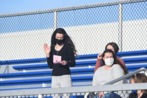 female student stands in bleachers with right hand raised