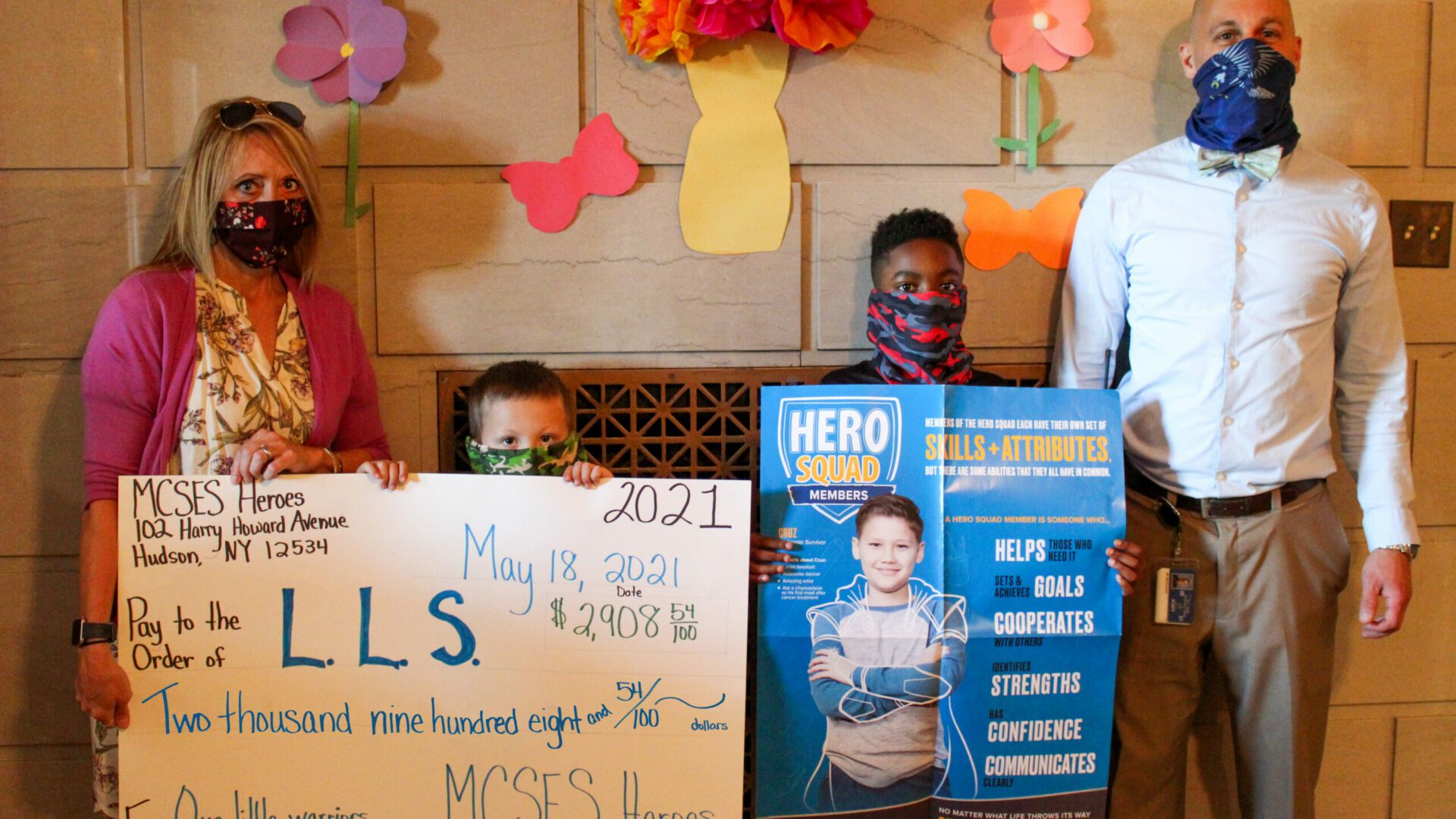 two elementary boys standing between adults and holding a big check totaling $2,908