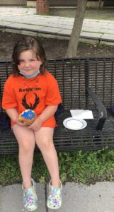 a young girl seated on a bench and holding a donut with blue frosting