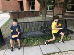 two elementary students seated on bench enjoying donuts