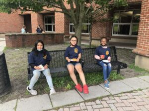 three elementary students seated on bench enjoying donuts