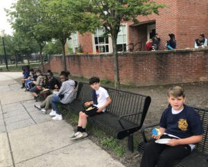 several elementary students seated on benches enjoying donuts