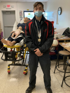 senior Jaxon Haigh poses with adult and baby CPR dummies on a stretcher